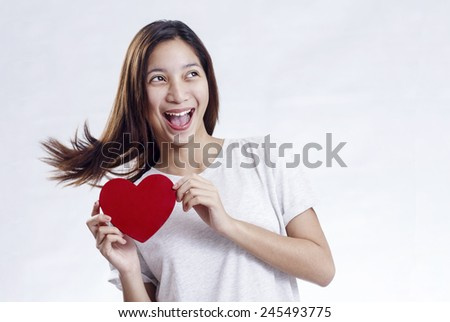 Joyful lady holding a heart shape red card for valentines day. - stock photo