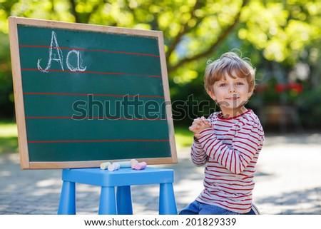 Joyful little boy at blackboard practicing writing letters, outdoor school or nursery. Back to school concept - stock photo