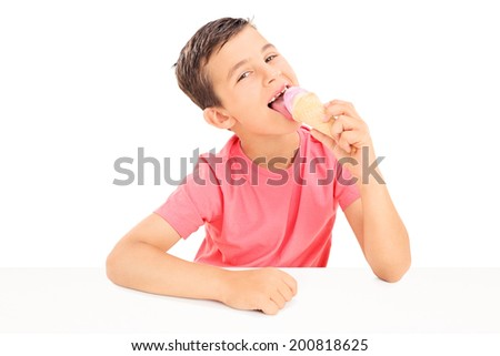 Joyful little boy eating an ice cream seated at a table isolated on white background - stock photo