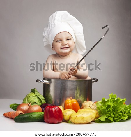 Joyful little boy in chef's hat sitting in large casserole and holding ladle - stock photo
