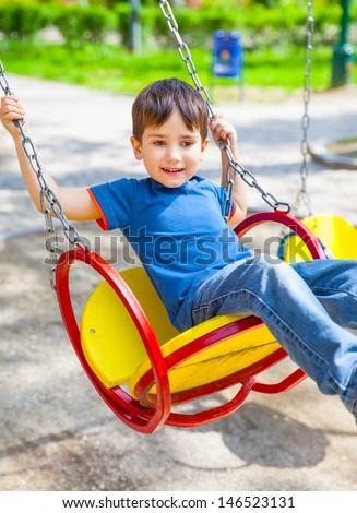 Joyful little boy swinging on a swing on a sunny day - stock photo