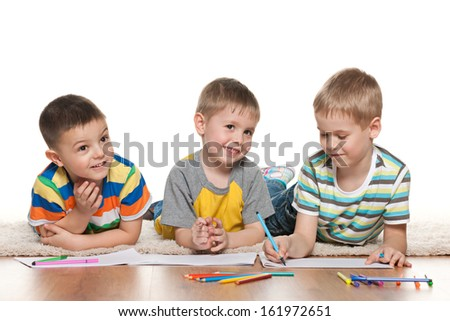 Joyful little boys are lying on the floor and draw on paper - stock photo