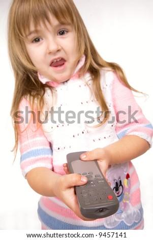 Joyful little girl holding tv remote control - stock photo