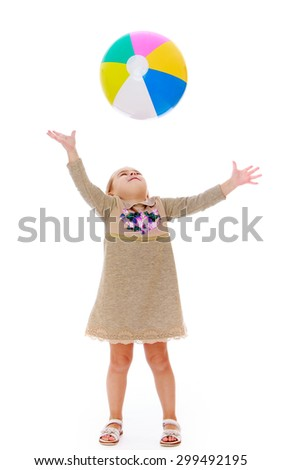 Joyful little girl in a long gray dress throw up a large inflatable striped ball , the girl is vacationing with his entire family at the resort-Isolated on white background - stock photo
