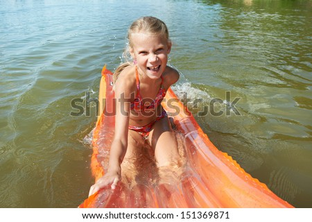 Joyful little girl on mattress in lake at summer