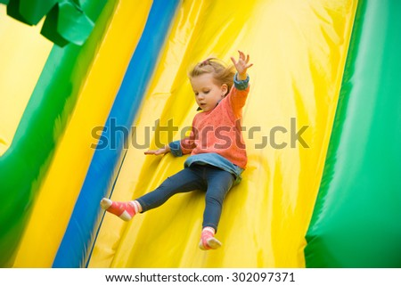 Joyful little girl playing on a trampoline. - stock photo