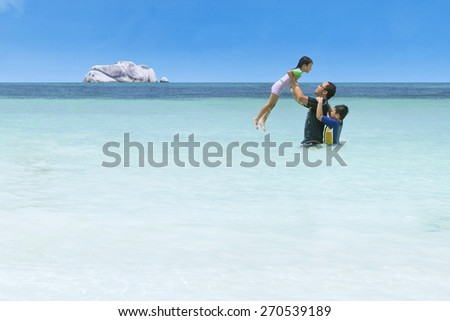 Joyful little girl playing on water with her family on the tropical beach - stock photo