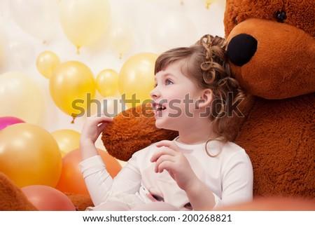 Joyful little girl posing hugging plush bear - stock photo