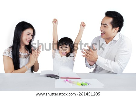 Joyful little girl raise her hands after finishing her schools assignment and get applause - stock photo