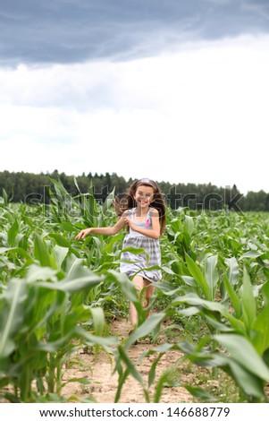 Joyful little girl running through the corn field - stock photo