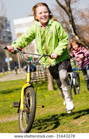 Joyful little girls riding on bicycles - stock photo