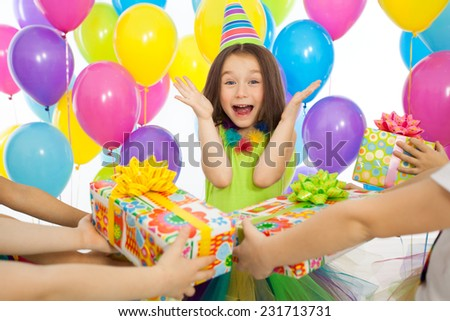 Joyful little kid girl receiving gifts at birthday party. Holidays, birthday concept. - stock photo