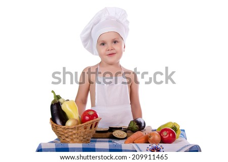 Joyful little kitchen boy preparing food in the kitchen at the table, isolated on white