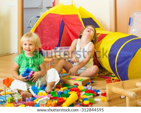 Joyful little siblings playing with toys together in home interior  - stock photo