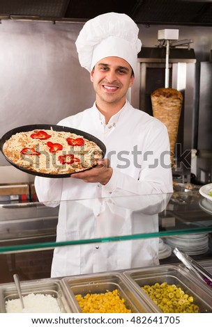 Joyful male chef holding baked Italian pizza at bistro
