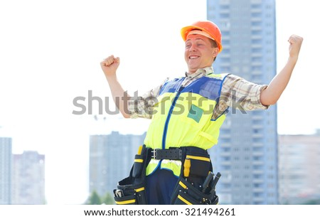 Joyful male construction worker. He raised his hands up in delight. They completed the construction. Happy contractor at a building site. Male construction worker at a building site smiling. Business.
