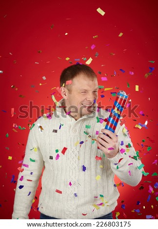Joyful man having fun with confetti cracker - stock photo