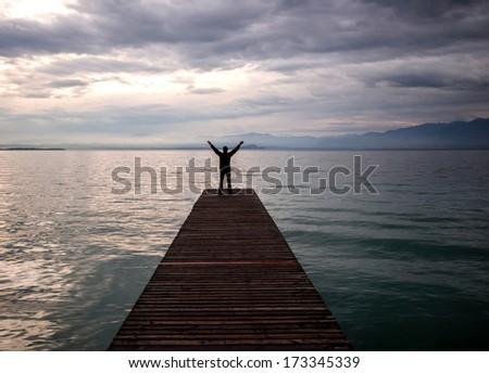 Joyful man with his hands in the air standing on dock - stock photo