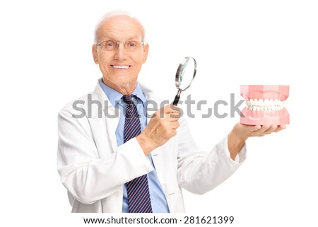 Joyful mature dentist holding a denture and a magnifying glass and looking at the camera isolated on white background - stock photo