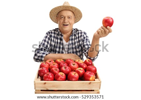 Joyful mature farmer holding an apple behind a crate filled with apples isolated on white background