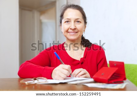 joyful mature woman with bill and money