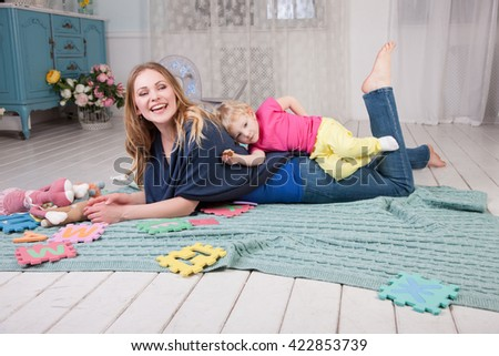 Joyful Mom and baby playing on the floor.Happy family mother playing with her baby. - stock photo