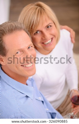 Joyful moment. Top view of pleasant cheerful content adult couple bonding to each other and drinking wine while evincing joy - stock photo
