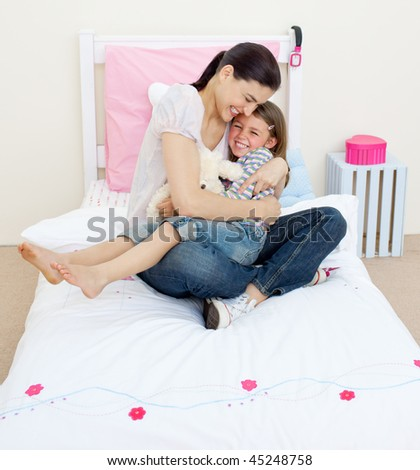 Joyful mother hugging her girl sitting on a bed - stock photo