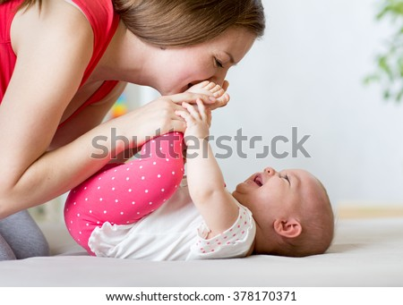 joyful mother playing with baby infant - stock photo