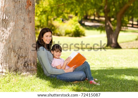 Joyful mother with her daughter in the park - stock photo