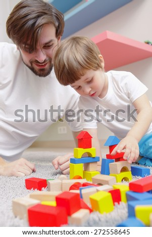 Joyful play. Young handsome father and son happily playing with a toy building kit at home - stock photo