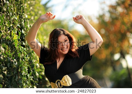 Joyful plus size woman outdoors. Shallow DOF. - stock photo