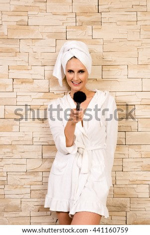 Joyful portrait of a gorgeous woman pointing with make-up brush towards the viewer in a short white bathrobe in front of stone wall - concept for beauty products and wellness. - stock photo