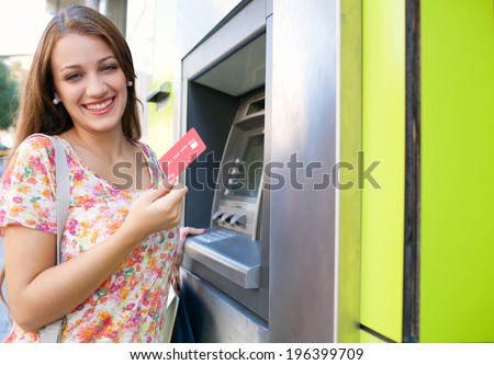 Joyful portrait view of an attractive young woman using a cash machine to withdraw cash money with her credit card, having fun and smiling in a city street. Outdoors finance and lifestyle. - stock photo