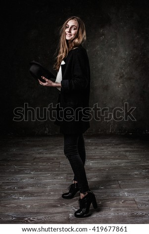 Joyful pretty girl wearing black classic hat smiling at camera - stock photo