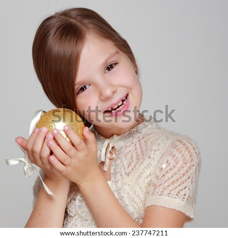 Joyful pretty little girl in a beautiful dress and a cute smile holding a yellow balloon for Christmas tree decorations on a gray background on Holiday - stock photo
