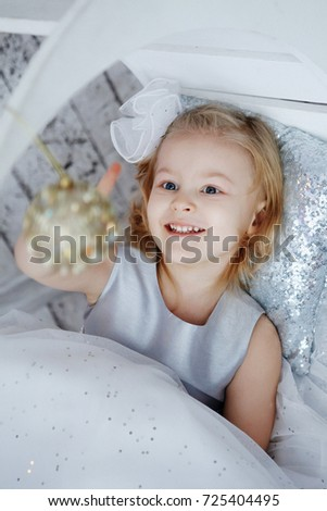 Joyful pretty little girl in a beautiful dress and a cute smile holding golden ball for Christmas tree decorations