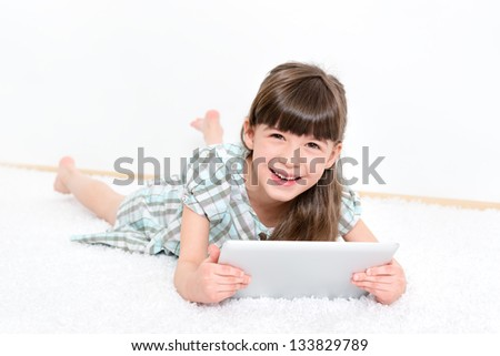 Joyful pretty little girl laughing as she lies on her stomach on a white carpet playing with a modern digital tablet in a white room. - stock photo