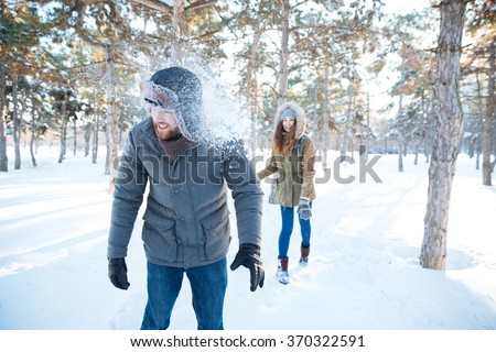 Joyful pretty young woman thowing snowballs in handsome happy young man in winter park - stock photo