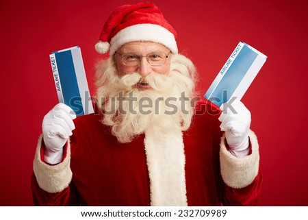Joyful Santa Claus with two airline tickets over red background - stock photo