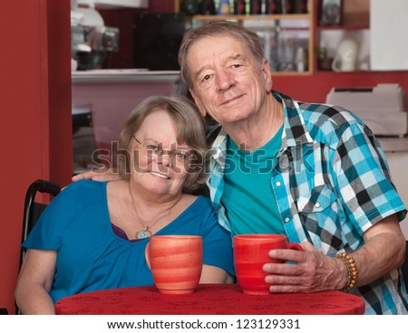 Joyful senior friends sitting with mugs at table - stock photo