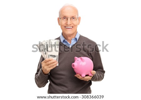 Joyful senior holding a few stacks of money in one hand and a piggybank in the other isolated on white background - stock photo