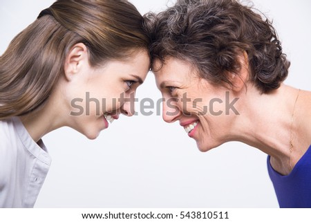 Joyful senior mother and daughter leaning heads