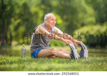 Joyful senior stretching his legs in a park and listening to music on headphones seated on the grass by a pond - stock photo