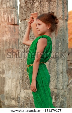 Joyful smiling girl in a beautiful emerald green dress with an amphora in the role of the Greek goddess/Ruins of the ancient city of Pantikapaion in the modern city of Kerch, Crimea - stock photo