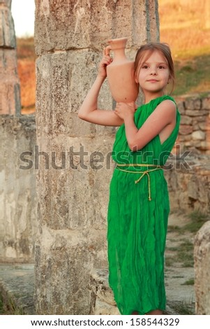 Joyful smiling girl in a beautiful emerald green dress with an amphora in the role of the Greek goddess/Ruins of the ancient city of Pantikapaion in the modern city of Kerch, Crimea, Ukraine - stock photo