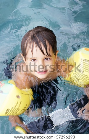 Joyful smiling little boy in swimming pool, outdoor shot - stock photo