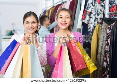 Joyful smiling young adults holding bags with purchases in apparel shop  - stock photo