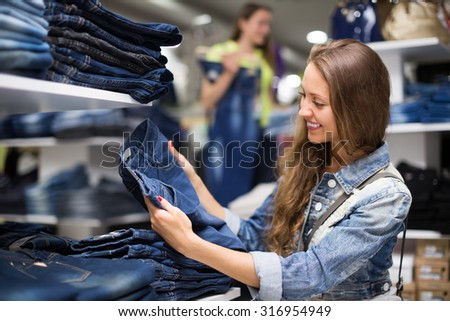 Joyful smiling young longhaired girl choosing new jeans at store