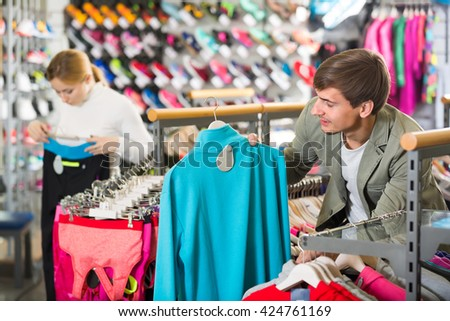Joyful smiling young man picking a cardigan in the sport shop